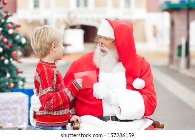 Side view of boy giving wish list to Santa Claus in courtyard