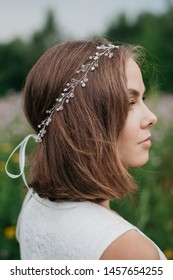 Side view of bride in simple wedding dress and hairstyle decorated by fancy hair accessory standing in field