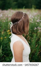 Side view of bride in simple wedding dress and hairstyle decorated by fancy beaded hair accessory standing in field