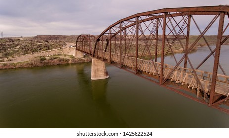 side view of a bridge as it is going over a river