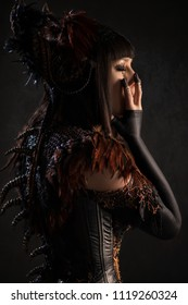 Side view of brunette woman in gothic steampunk gown posing at camera