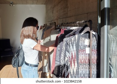 Side view of brunette woman in sunglasses looking at sweater on rack of clothes in store in sunlight.