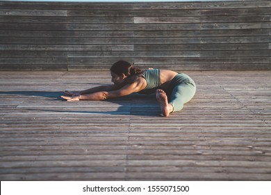 Side view of brunette woman in yoga clothing stretching legs in seated wide legged forward bend on wooden floor in front of lumber fence