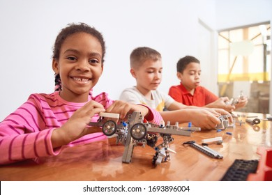 Side view of building kit for group of three multiracial kids creating toys, having positive emotions and joy, african girl smiling and looking at camera. Close up of friends working on project.