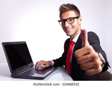 side view of a business man working on laptop and making the ok gesture