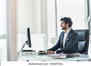Side view of a business partner sitting at his tidy glass desk in a white office with large windows He has a beard and is wearing a dark suit with shirt He is answering his emails on his computer