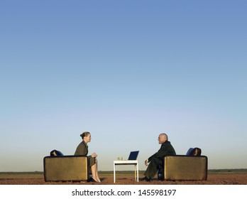 Side view of business people on armchairs communicating on field