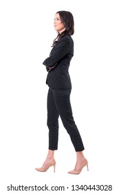 Side view of business woman with crossed arms walking, smiling and looking away. Full body isolated on white background.