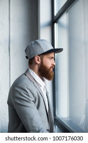 side view of businessman in baseball cap looking at window