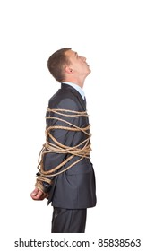 Side view of businessman executive tied up with rope, looking up