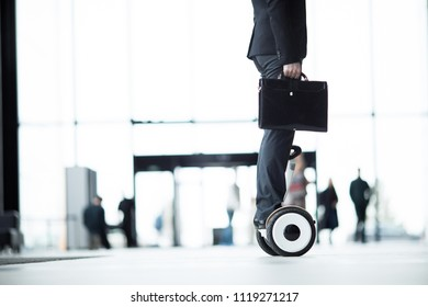 Side view of businessman in formalwear standing on hoverboard and moving straight