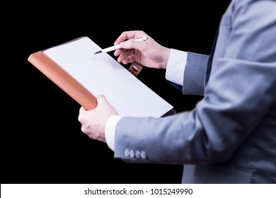 Side view of a businessman in grey suit pointing with pen on paper on black background.