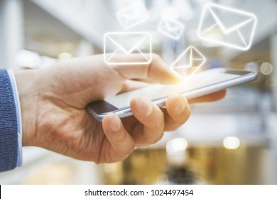 Side view of businessman hand using smartphone with creative e-mail network. Email communication concept