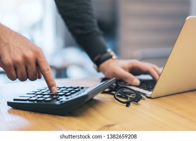 Side view of businessman hands using laptop and calculator on wooden desktop. Accounting and finance concept