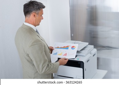 Side view of businessman looking at paper with graphs while standing by color printer