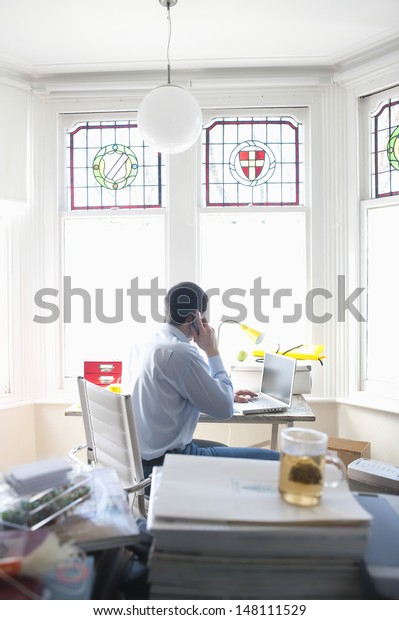 Side view of businessman on call while using laptop in home office