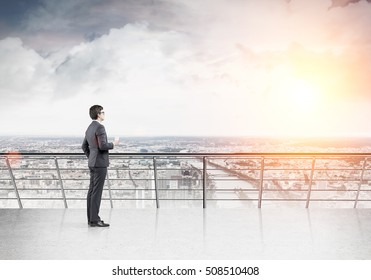Side view of businessman with paper cup of coffee standing on balcony and looking at large city. Mock up. Toned image