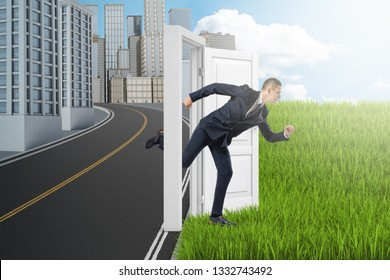 Side view of businessman running from modern city to green field through door standing alone between them with no wall. Choose your lifestyle. Office versus freelance. Holidays begin.