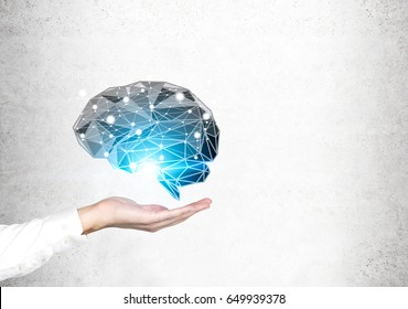 Side view of businessman s hand holding a black brain hologram shining with a blue light near a concrete wall. Mock up