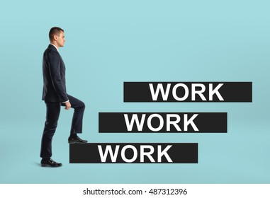 Side view of a businessman stepping up career ladder with 'work' words on the steps. Professional, expert, pro. Success and advancement. Self-improvement.