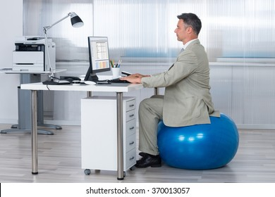 Side view of businessman using computer while sitting on exercise ball at office
