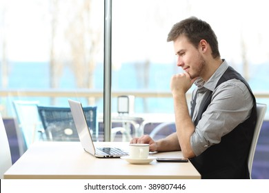 Side view of a businessman using a laptop on line sitting in a bar with a window and the sea in the background