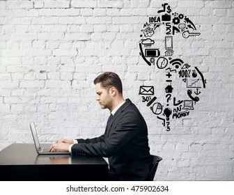 Side view of businessman using laptop at desk placed against white brick wall with dollar sign sketch. Financial growth concept