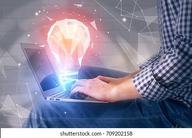Side view of businessman using laptop with abstract polygonal lamp on white brick wall background. Idea concept. 3D Rendering
