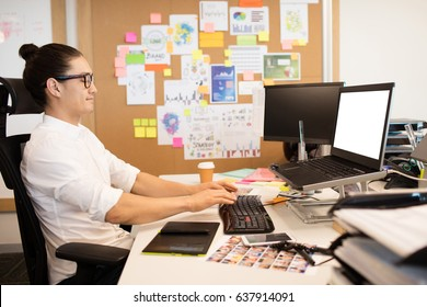 Side view of businessman working at creative office desk