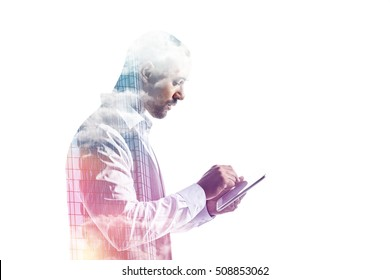 Side view of businessman working on a tablet pc double exposure sky and glass facade