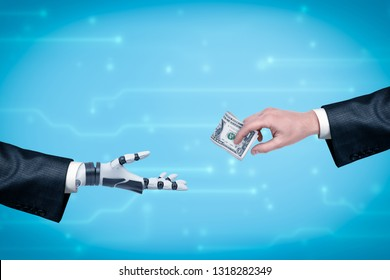 Side view of businessman's hand giving money to robot's hand on blue background with blurred microcircuit lines. Humans and AI cooperate. Businessmen invest in AI. New market relations.