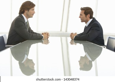 Side view of businessmen looking at each other in conference room