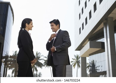 Side view of businesswoman and businessman standing outside building