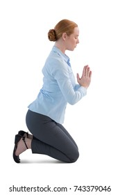 Side view of businesswoman kneeling in prayer position