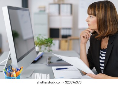 Side View of a Businesswoman Looking at her Computer Screen Seriously While Holding Documents.