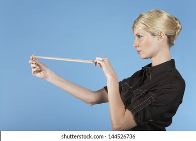 Side view of a businesswoman shooting rubber band on blue background