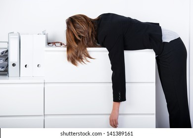 Side view of businesswoman sleeping on counter in office