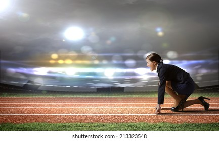 Side view of businesswoman at stadium standing in start position