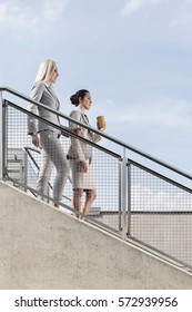 Side view of businesswomen moving down stairs against sky