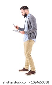 Side view of busy bearded businessman using tablet and smart phone walking. Full body length portrait isolated on white studio background.