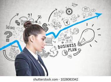 Side view of a calm and beautiful young european woman with a bun wearing a white sweater. A concrete wall background with a business plan sketch