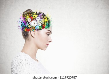 Side view of a calm and beautiful young european woman with a bun wearing a white sweater. Colorful brain sketch with cogs inside her head. Creative thinking concept. Mock up