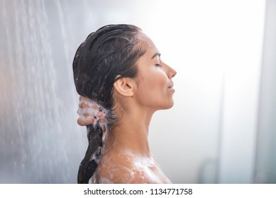 Side view calm girl using shampoo during taking shower. She having leisure there