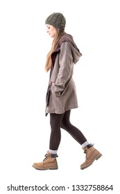 Side view of calm or sad hipster girl in winter warm clothes walking and looking down. Full body isolated on white background.