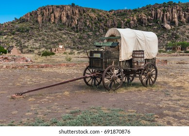 Side view of canvas covered wagon with green buck board and large wooden barrel on the side setting in Fort Davis with mountains in the background