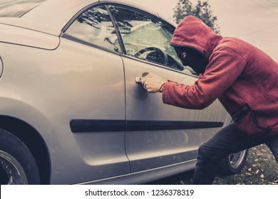 Side view of car being forced by a man in hoodie and mask. Thief tries to steal vehicle from a parking. Young male acts alone breaking the car door. Unknown person picklocks the automobile. Car fraud