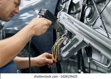 Side view of car electric repairman holding and using the soldering iron to blend the wires for repairing signaling in disassembled door of auto. Servicing of electronic devices concept