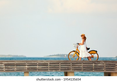 Side view of carefree female in white dress and sunhat walking with bike along wooden embankment near sea at sunset