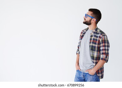 Side view of casual bearded man wearing blue glasses posing isolated against white background. Man holding hands in pockets