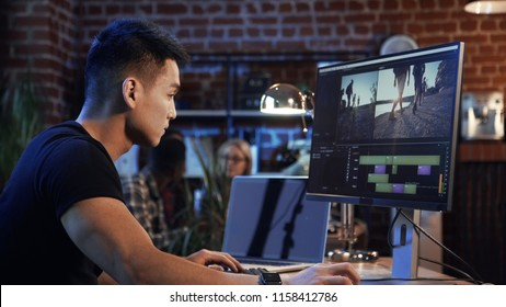 Side view of casual confident Korean man working on computer with video editing and color correction